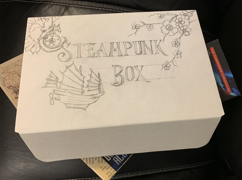"""White box labeled """"Steampunk Box"""" in vintage font with pencil sketch of dragon and clock, Chinese junk and cherry blossoms"""